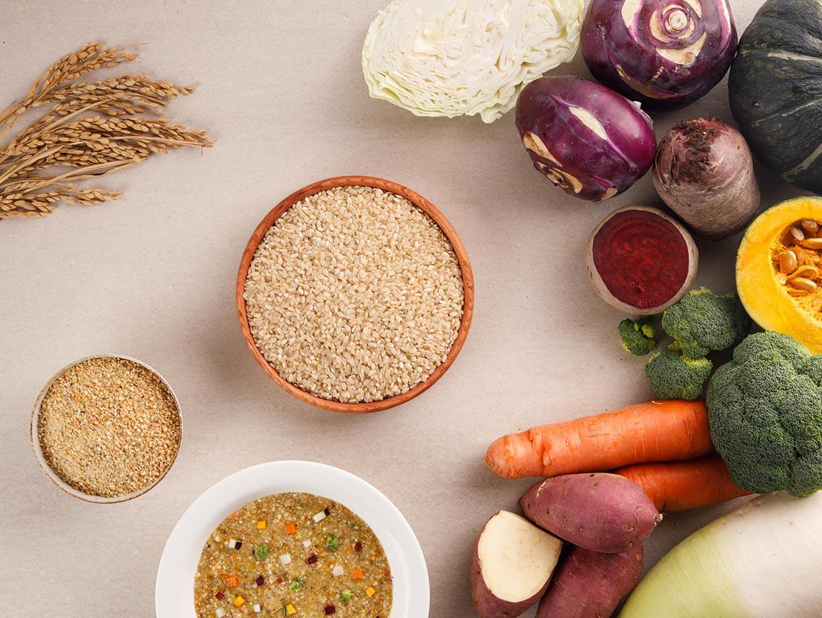 각종 채소들이 바닥에 놓여져 있고 그 옆에 가지런히 담아놓은 현미채소죽