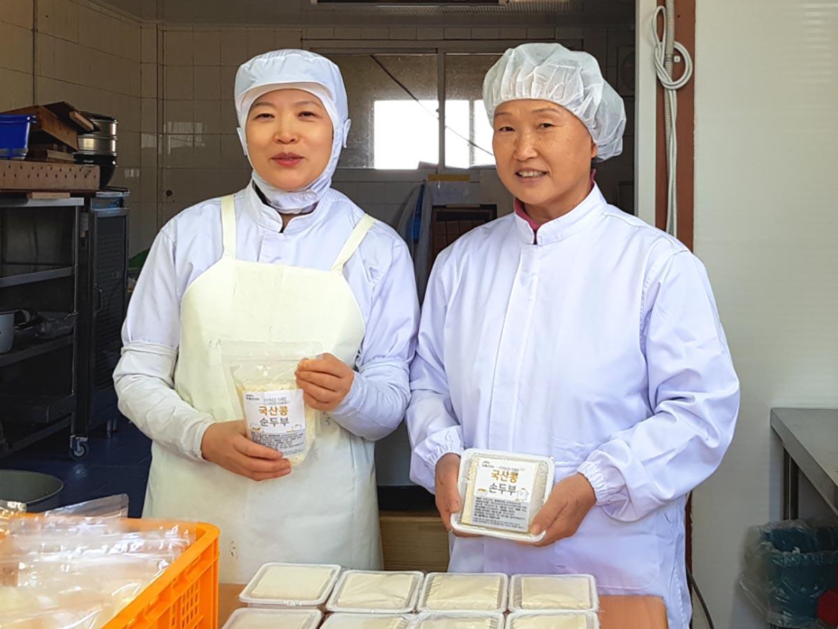 산골방앗간 직원들이 위생복을 입고 산골방앗간 제품을 들고 있는 사진